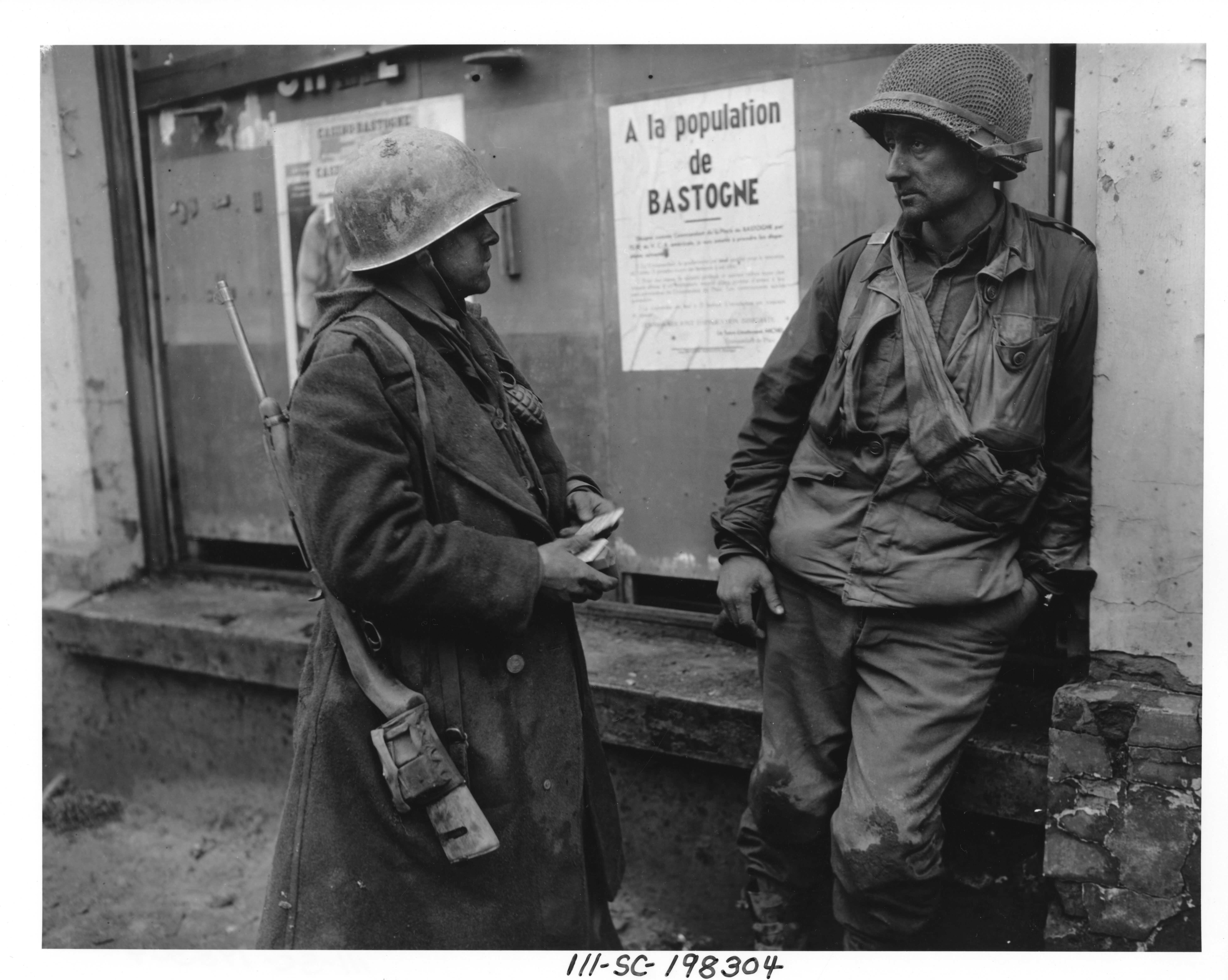 Original caption: Bastogne, Belgium-Weary infantrymen of the 110th Regt., 28th Div., US 1st Army following the German breakthrough in that area. The enemy overran their battalion. (L-R) Pvt. Adam H. Davis and T/S Milford A. Sillars. Dec. 19, 1944