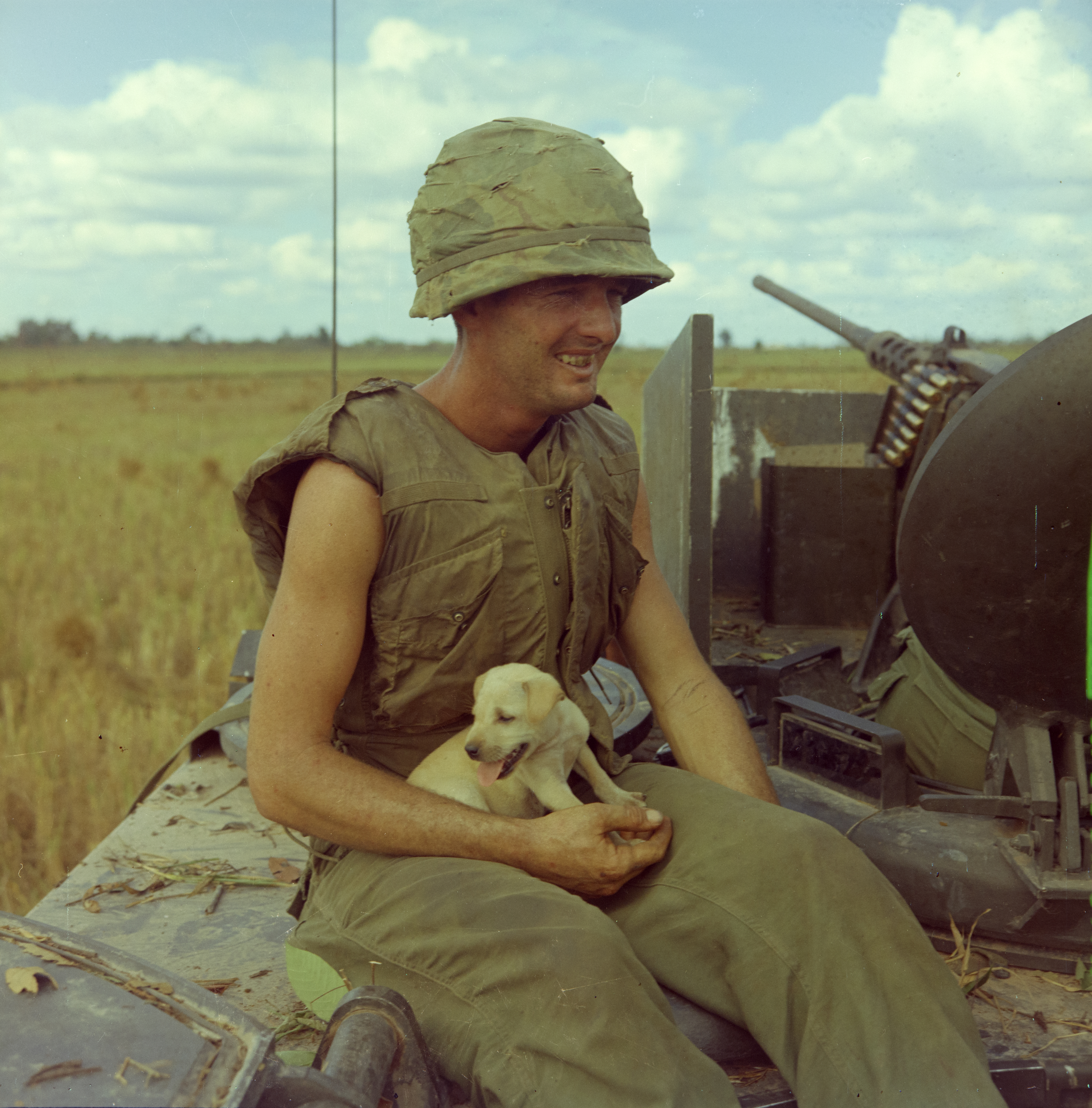 Specialist 4th Class Holding a Dog after an Airstrike in a Village Near Laikhe – 1966