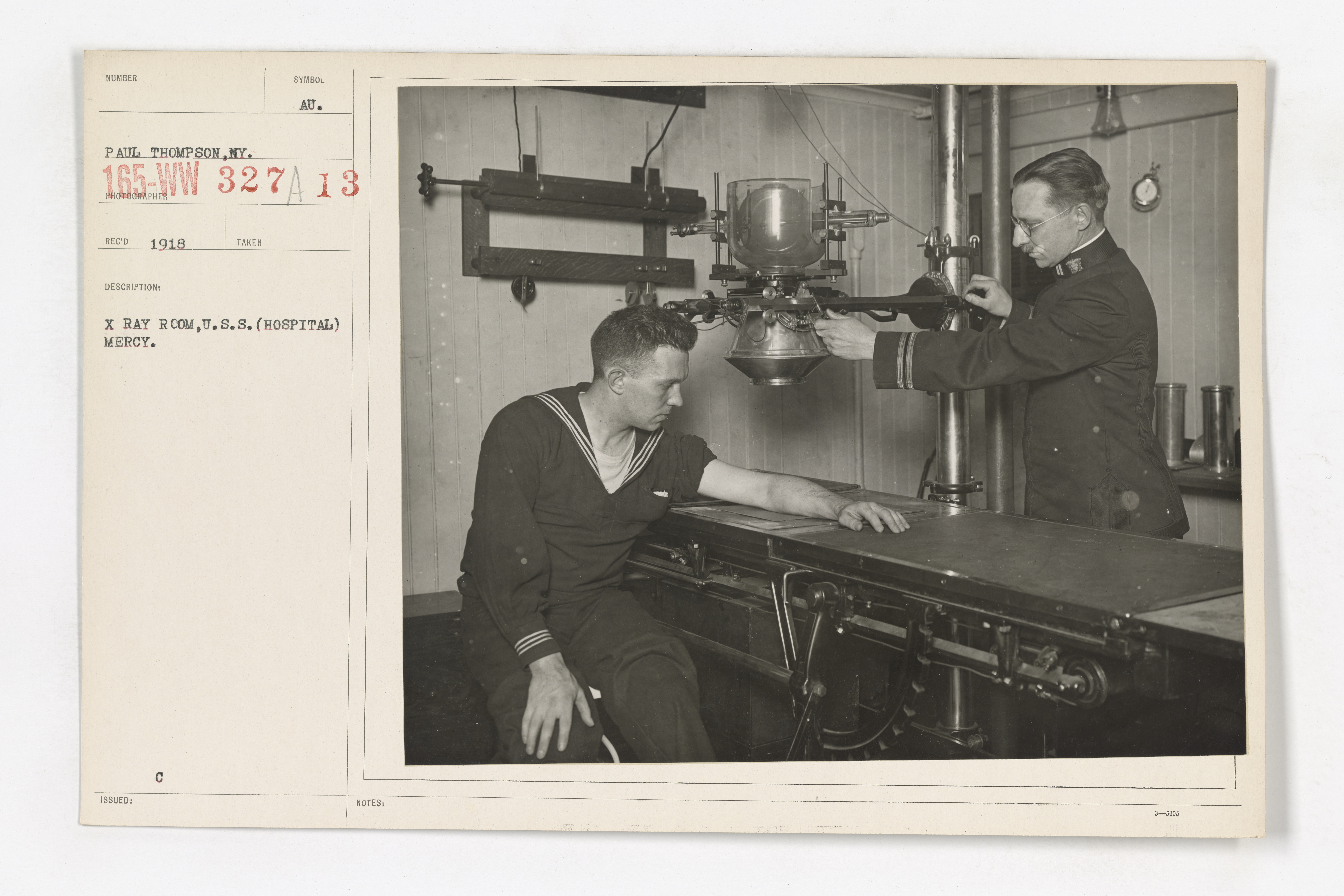 black and white photo of doctor x-raying a Navy man's arm