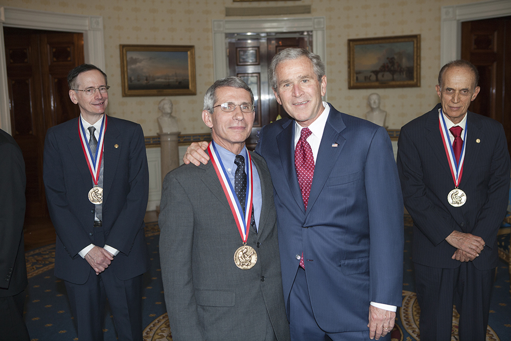 In this photograph President George W. Bush poses with 2005 National Medal of Science recipient Dr. Anthony S. Fauci of The National Institute of Allergy and Infectious Diseases in the Blue Room, after award ceremonies in the East Room of the White House. Also pictured are Dr. Tobin J. Marks (left) and Dr. Bradley Efron (right).
